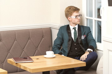 Young handsome stylish man in cafe with coffee