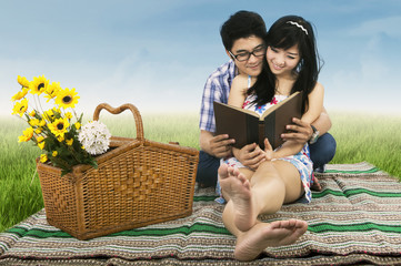 Young couple is reading book outdoors
