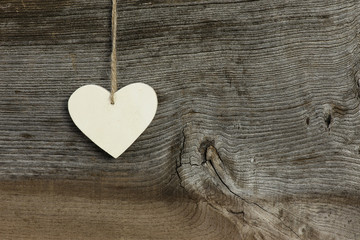 White Love Valentine's heart hanging on wooden texture backgroun