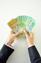 Hands holding money - Australian dollars