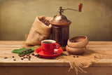 Cup of coffee and grinder with coffee beans on wooden table