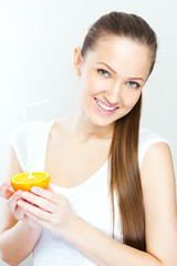 Attractive smiling young woman drinking orange juice straight fr