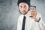 Businessman taking self portrait with mobile phone