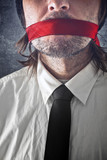 Businessman with red strip over mouth