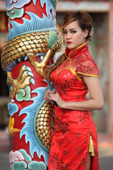 Woman in Chinese dress stand beside a pole