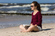 Teenage girl reading book sitting on beach