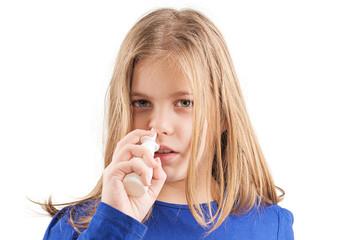 Sick girl taking a nasal spray