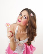 Attractive girl with a lollipop in her hand and pink dress