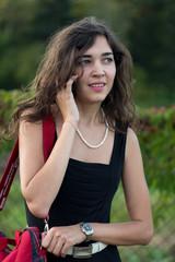 Молодая девушка в парке разговаривает по мобильному телефону