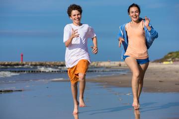 Teenage girl and boy jumping, running on beach