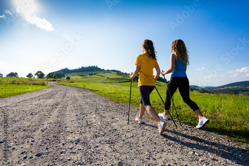 Leinwandbild Motiv Nordic walking - active people working out outdoor