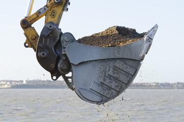 Excavator dredging a harbor