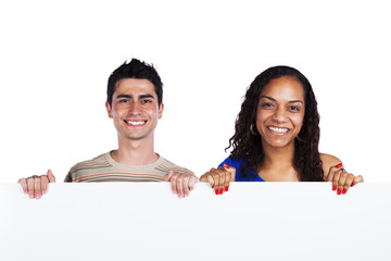Multiracial couple holding a blank banner