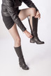 Woman wearing black fishnet tights fastening leather boots