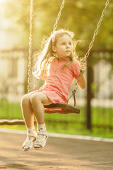 Pretty little girl swinging on seesaw beneath bright shining