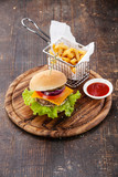 Burger and French fries in basket on wooden background