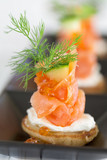 Blini with smoked salmon and sour cream, garnished with dill and