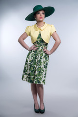Retro 50s fashion brunette girl with hat wearing green dress and