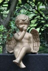 Engel sitzt auf Grabstein und lutscht am Daumen