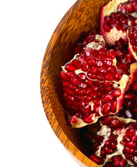 broken pomegranate in a wooden bowl