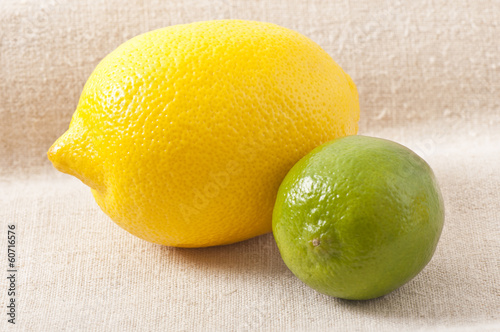 ripe, fresh lemon and lime on a background of old cloth