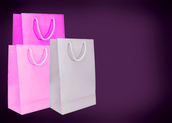 Pink paper bags on dark background.