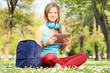 Young female student with headphones and tablet in park
