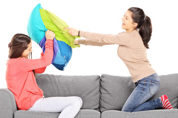 Two young girls having a pillow fight seated on couch