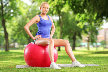 Young female athlete sitting on a ball and looking at camera in