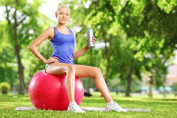 Young female athlete sitting on fitness ball holding a bottle