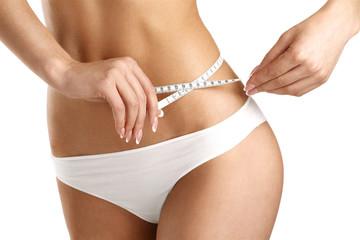 Closeup of a woman measuring her hips