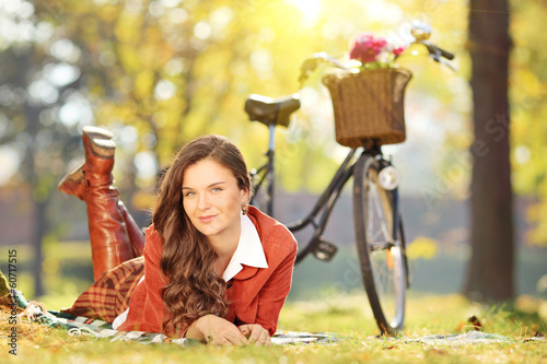 Young female relaxing on a grass with bicycle in park