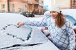 Woman standing near snowy car and windshield with drawing heart
