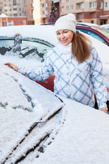 Attractive woman and snowy car with drawing heart shape on glass