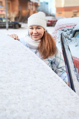 Happy smiling woman standing near of snow covered car