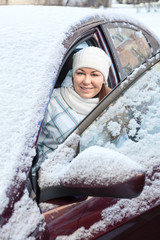 Pretty woman sitting inside of snow covered car