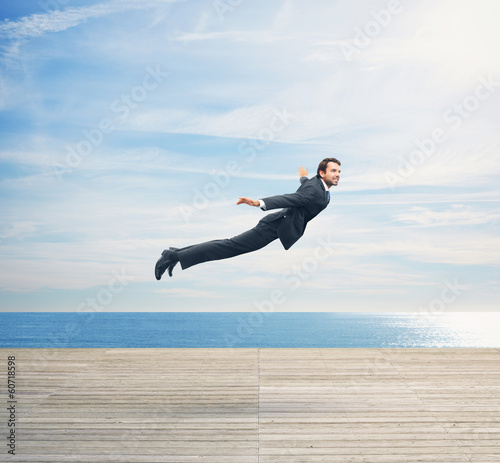 Man in suit flying over boardwalk