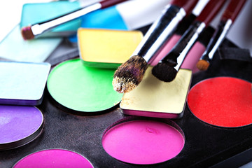 Makeup brushes with colorful eyeshadows, close-up