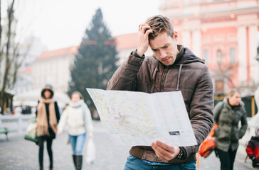 Lost tourist looking at city map on a trip. Looking for directio