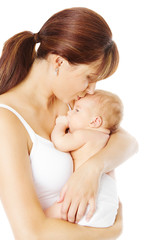 Mother kissing newborn baby holding in hand, white background