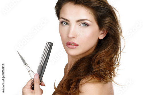 Beautiful woman holding scissors and comg in her hand