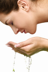 Beautiful woman refreshing her face with water