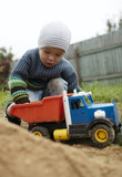 Boy playing with toy truck outdoor poster