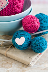 Bright balls of yarn in blue plates and heart made of felt