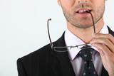 Man biting glasses