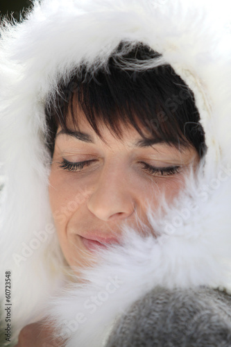 Woman wearing coat with furry hood