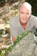 Man kneeling behind a boulder
