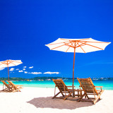 Wooden chairs and umbrellas on white sand beach facing the