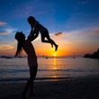 Silhouette of mother and little daughter playing on the beach of