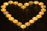 tea lights in the shape of a heart on wood background